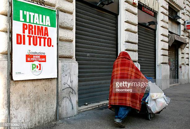A homeless person pushes a trolley past a poster reading 'Italy first of all' in Rome Italy on Monday Nov 14 2011 Former European Union Competition...