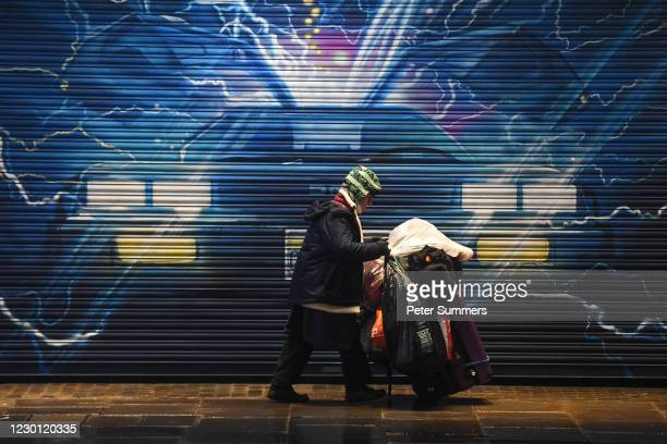 Homeless person pushes their belongings past a Back to the Future mural on December 13, 2020 in London, England. The number of new rough sleepers has...