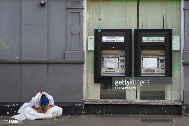 Homeless person sits near Barclays Bank cash machine in London.