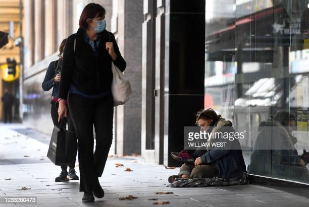 Homeless person sits on the pavement in Melbourne's normally bustling city centre on June 4 as the coronavirus lockdown of Australia's second-biggest...