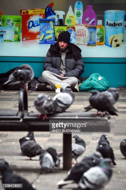 A homeless person sits with pigeons in a Glasgow city centre street on March 27 2020 Britain is under lockdown its population joining around 17...