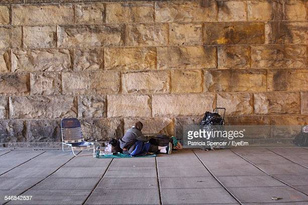 homeless person sitting on sidewalk against stone wall - homeless person stock pictures, royalty-free photos & images