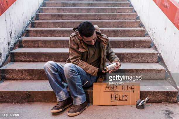 homeless person sitting on stairs with cardboard and donation can - homeless veterans stock photos and pictures