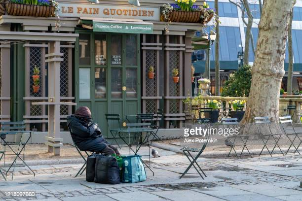 a homeless person sleeping in bryant park deserted because of the covid-19 pandemic. - alex potemkin coronavirus stock pictures, royalty-free photos & images