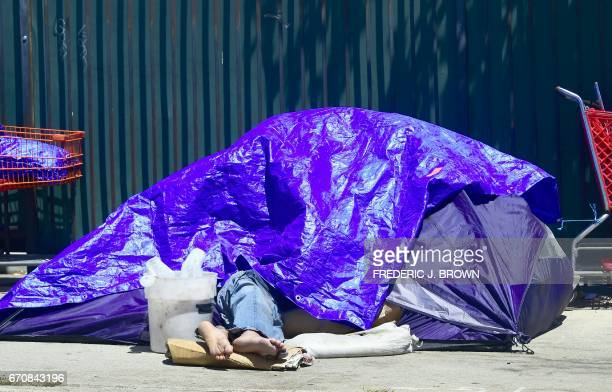 A homeless person sleeps beneath a tarp covering a tent lining sidewalks in downtown Los Angeles California on April 20 where the city's mayor Eric...