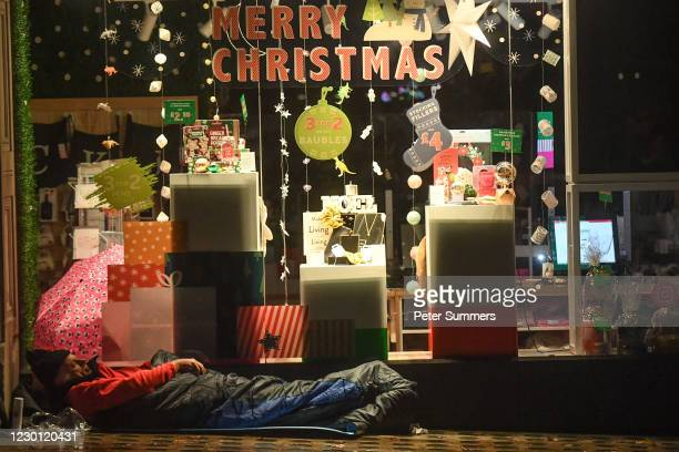 Homeless person sleeps in front of a christmas display in a shop window on December 13, 2020 in London, England. The number of new rough sleepers has...