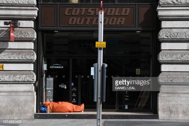 Homeless person sleeps in the doorway of a closed store on Regent Street in London's main high street retail shopping area on May 22, 2020 as...