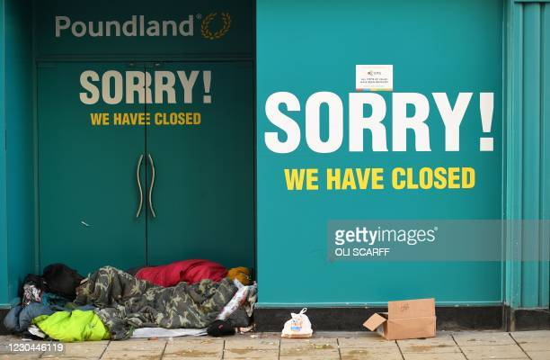 Homeless person sleeps in the doorway of a closed-down Poundland store in York, north west England on January 6 on the second day of Britain's...