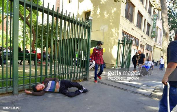 A homeless person sleeps on the street in Skid Row downtown Los Angeles California on October 16 2018 Unsanitary conditions of street encampments for...