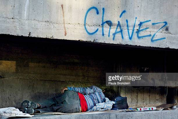 A homeless person sleeps under a bridge with Chavez graffiti December 28 2002 in Caracas Venezuela Business labor and opposition political parties...