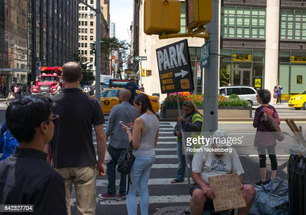 A homeless person solicits donations lower right as pedestrians wait for a traffic light to change August 28 2017 in New York City It's estimated...
