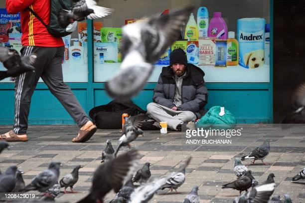 A homeless person watches pigeons in a Glasgow city centre street on March 27 2020 Britain is under lockdown its population joining around 17 billion...