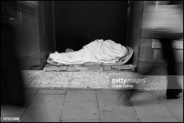 Homeless person wrapped in a white blanket, like a shroud, in a doorway.