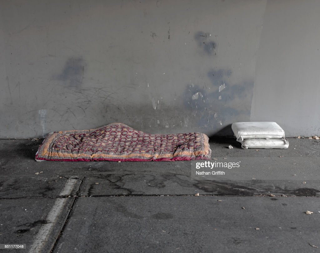 homeless person's bed and pillows under bridge : Stock Photo