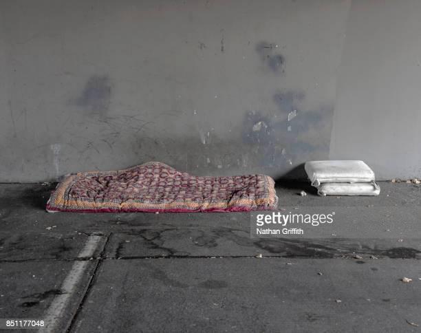 homeless person's bed and pillows under bridge - sin techo fotografías e imágenes de stock
