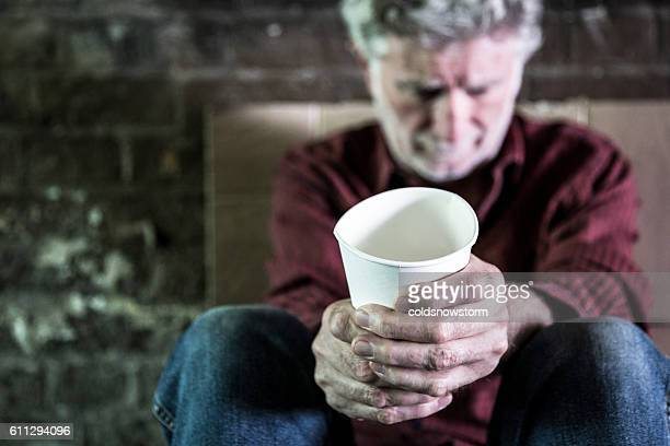 Homeless senior adult man begging for money with paper cup