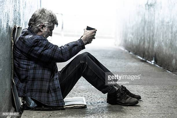 homeless senior adult man sitting and begging in subway tunnel - homeless stock photos and pictures