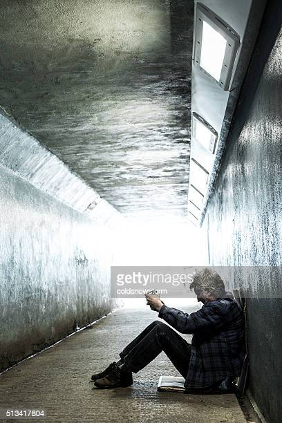 Homeless senior adult man sitting and begging in subway tunnel