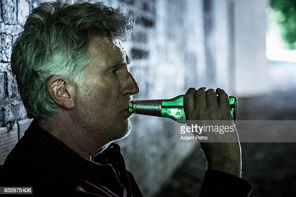 Homeless senior adult man sleeping rough drinking from beer bottle