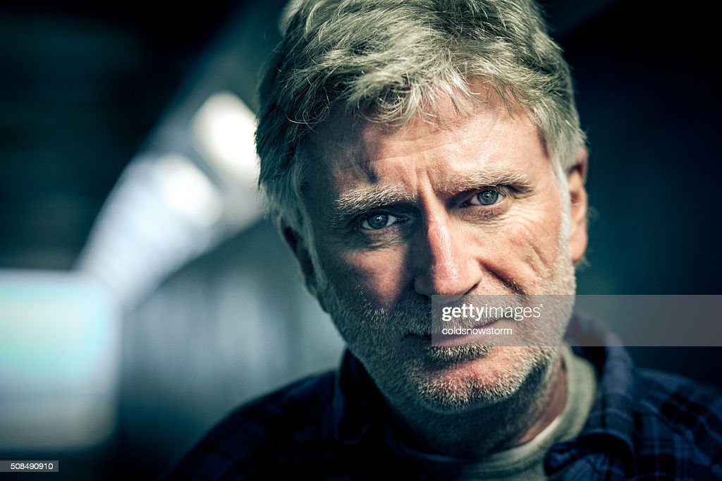 Homeless senior adult man with beard in subway tunnel : Stock Photo