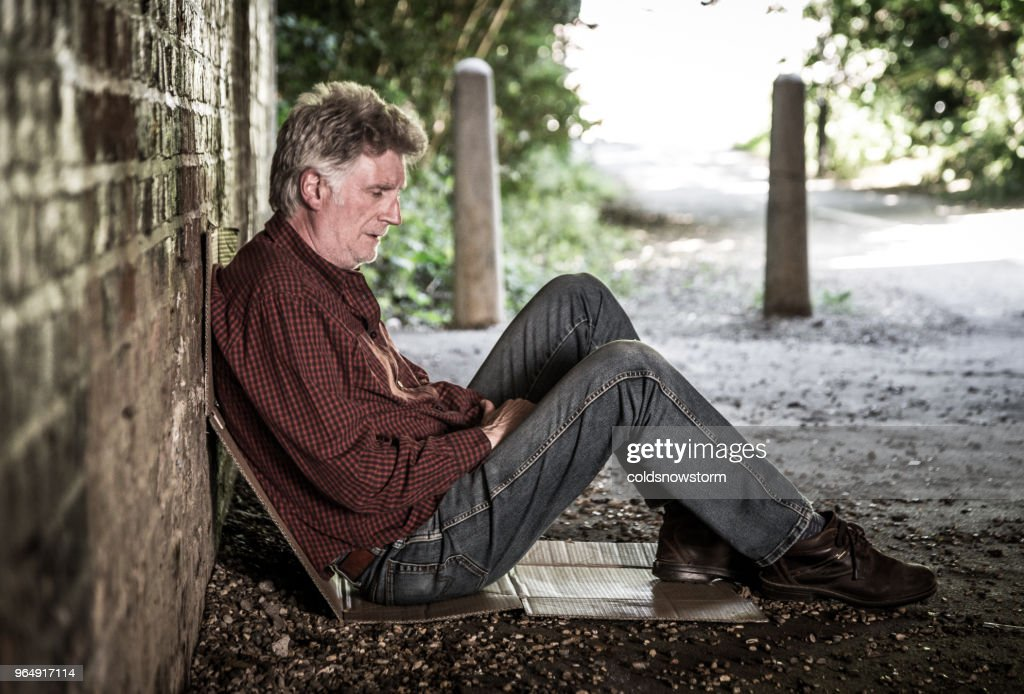 Homeless senior male sleeping rough in dark subway tunnel : Stock Photo
