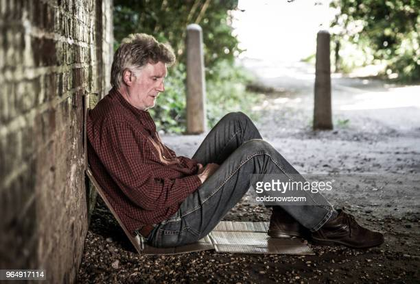 homeless senior male sleeping rough in dark subway tunnel - addict stock photos and pictures