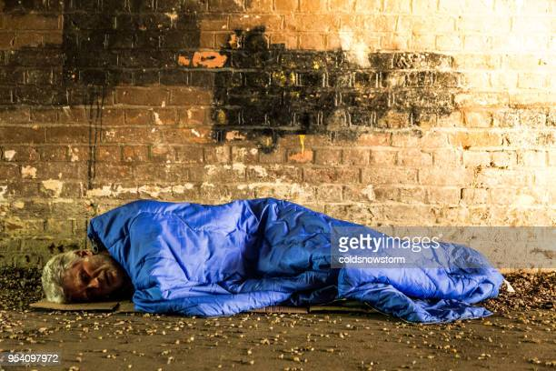 homeless senior male sleeping rough in subway tunnel - homeless foto e immagini stock