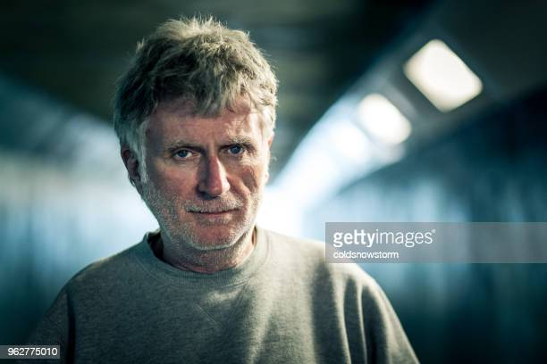 homeless senior male standing in dark subway tunnel - male bum stock pictures, royalty-free photos & images