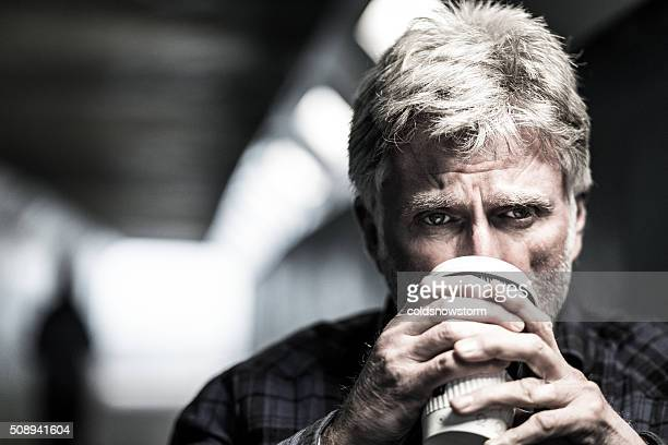 Homeless senior man begging with paper cup in subway tunnel