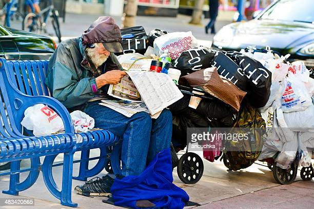 homeless senior man sitting on bench, reading newspaper - homeless los angeles stock photos and pictures