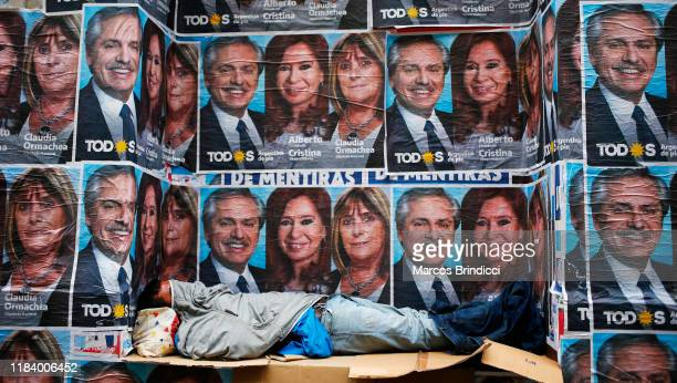 A homeless sleeps next to posters advertising winning ticket of Frente de Todos represented by Alberto Fernandez and Cristina Fernandez on October 28...