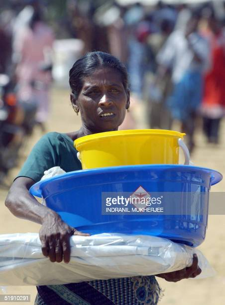 A homeless Sri Lankan tsunami survivor carries back non food relief item at the central college camp in the Liberation Tigers of Tamil Eelam...