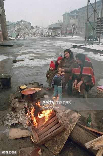 Homeless survivors sit around a fire in the street near their collapsed apartment building and wait to hear of family members feared trapped in the...