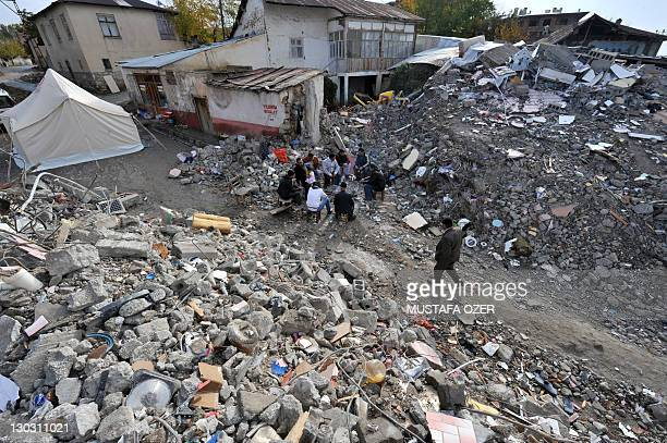Homeless survivors sit on their collapsed building after an earthquake in Ercis province of Van on October 26 2011 Homeless survivors of Turkey's...
