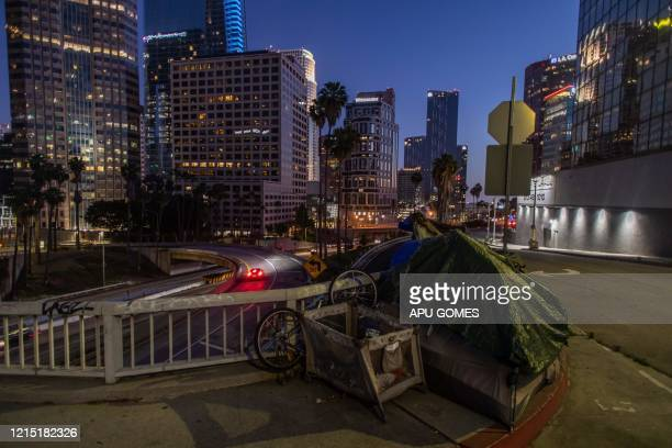 A homeless tent is seen at dusk next to the 110 Freeway during the novel Coronavirus COVID19 pandemic in Los Angeles California on May 25 2020 On May...