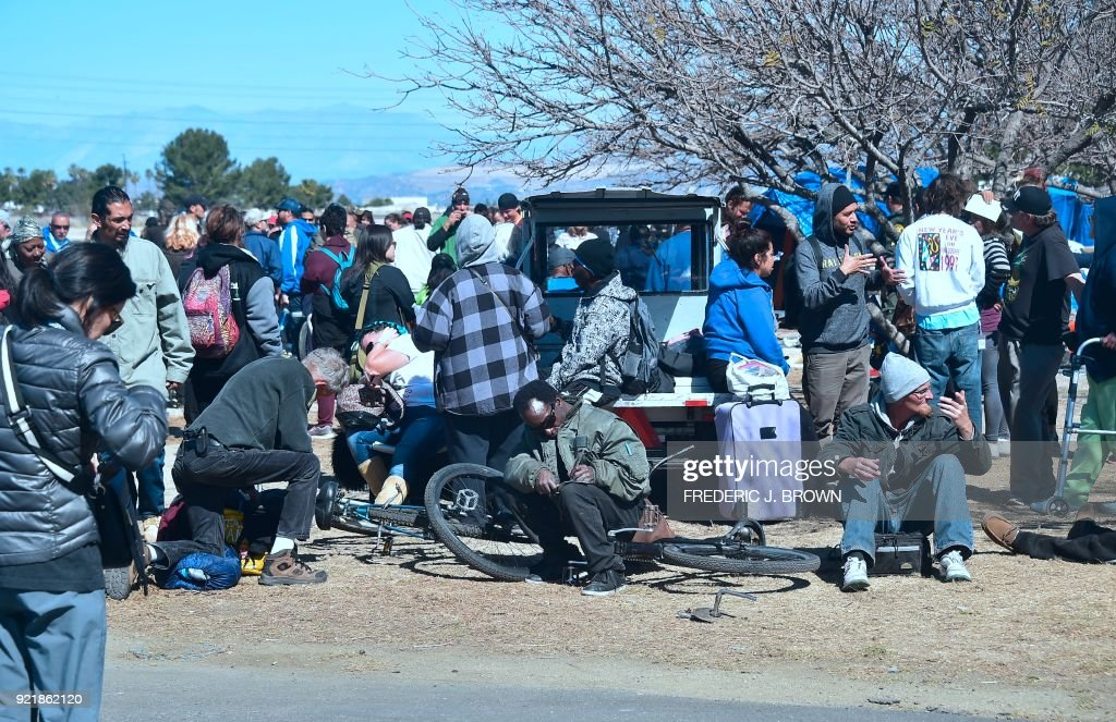 Homeless transients wait to be taken away on buses from the Shomeless encampment beside the Santa Ana River on February 20, 2018 in Anaheim, California. Officials in Orange County began moving homeless transients out of the homeless tent encampments to shelters or motels as part of the settlement worked out by homeless advocates and the county under supervision of a federal court judge. / AFP PHOTO / Frederic J. BROWN