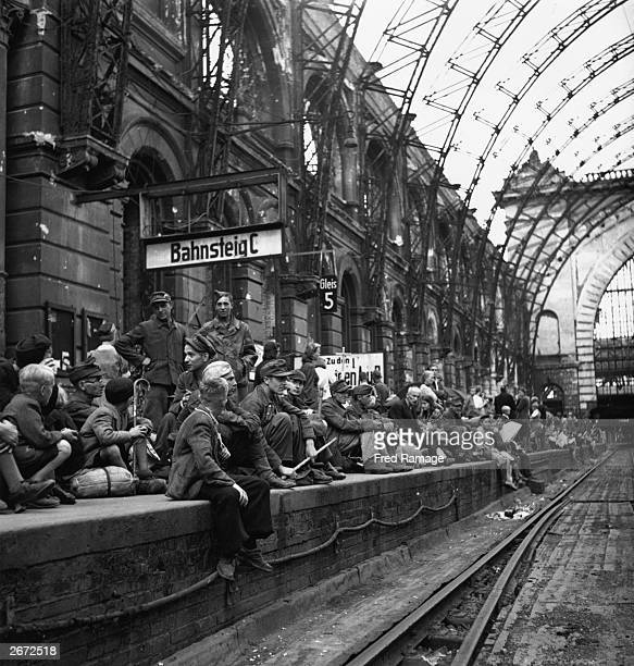 Homeless travellers fill a dilapidated Berlin railway station platform shortly after Germany's defeat in World War II They are poorly dressed and...