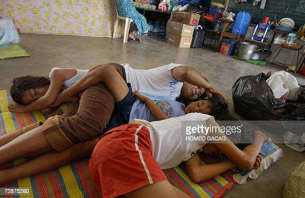 Homeless typhoon victim mother Marilyn Mirante rests with her three children from right Arjelyn Jomari and Christine at a school clasroom converted...