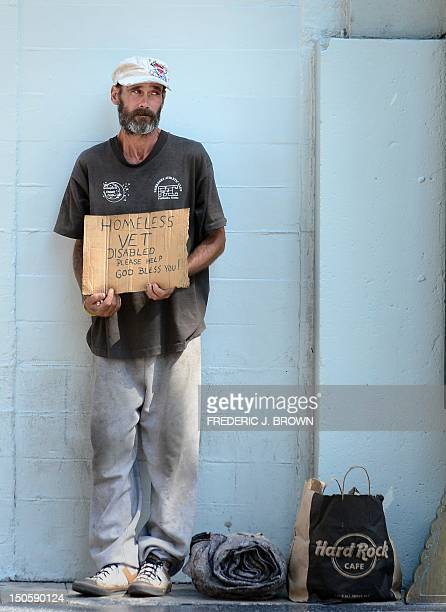 A homeless war veteran explains his plight hoping for assistance while standing along Hollywood Boulevard in Hollywood California on August 22 2012...