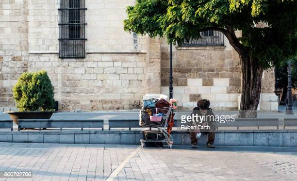 homeless with his cart at the street - homelessness stock pictures, royalty-free photos & images