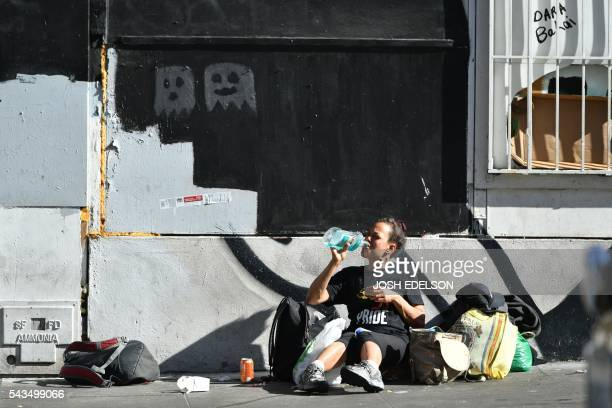 A homeless woman drinks mouth wash along a sidewalk in downtown San Francisco California on June 27 2016 Homelessness is on the rise in the city...