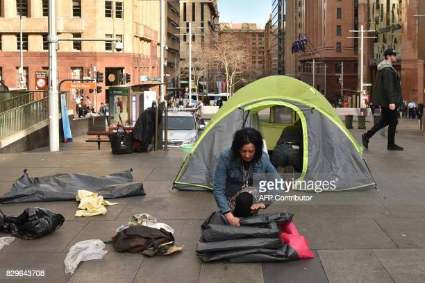 A homeless woman packs up her belongings in Martin Place which has become known as 'Tent City' in the central business district of Sydney on August...