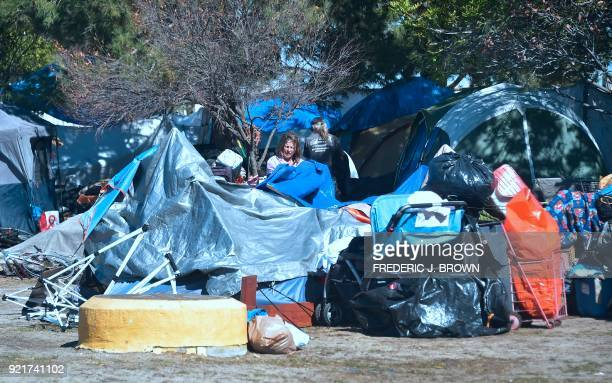 A homeless woman packs up her tent and belongings at the homeless encampment beside the Santa Ana River in Anaheim California on February 20 2018...