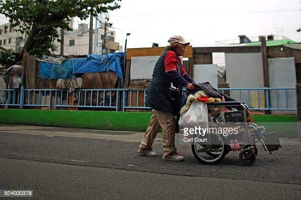 A homeless woman pushes a wheelchair past the slum area of Kamagasaki on April 24 2016 in Osaka Japan Kamagasaki a district in Japan's second largest...