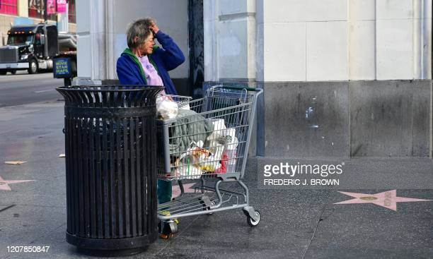 A homeless woman reacts beside a trash can along Hollywood Boulevard in Hollywood on March 20 a day after Los Angeles County announced a nearlockdown...