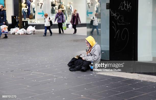 homeless woman reading book - edinburgh scotland stock photos and pictures