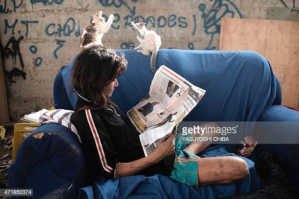 A homeless woman reads a newspaper sitting on a couch in the open amid the debris of her shack on April 30 2015 early morning in Rio de Janeiro...