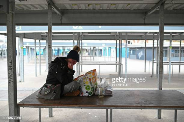 Homeless woman sits on a table in a deserted market in Ashton-under-Lyne east of Manchester in north-west England on November 11 as people in England...