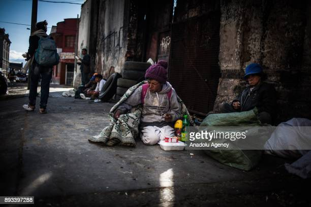 A homeless woman sits on the ground and eats her food distributed by volunteers from 'El Banquete del Bronx' in Bogota Colombia on December 15 2017...