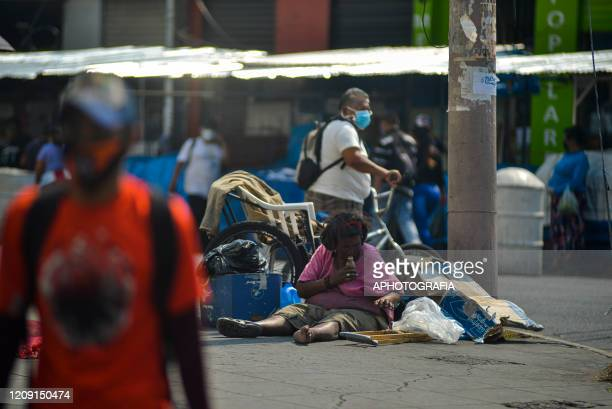 A homeless woman sits on the street where she will live through the COVID19 crisis on April 2 2020 in San Salvador El Salvador On March 21st...
